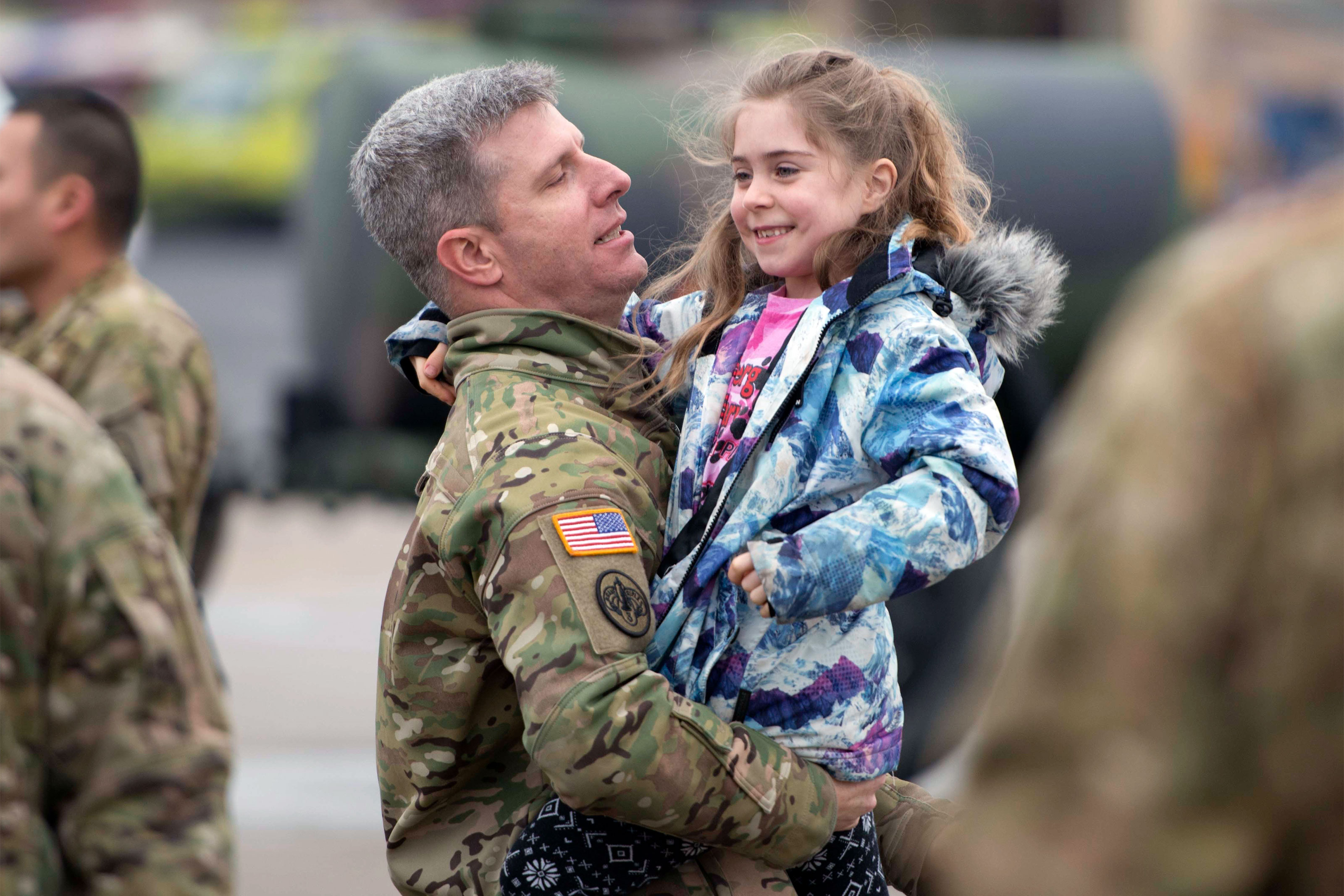 "CW3 Erik Herr carries his excited daughter on the annual 1-214th GSAB on their annual ""Family Safety Day"". (U.S. Army/Paul Hughes)"