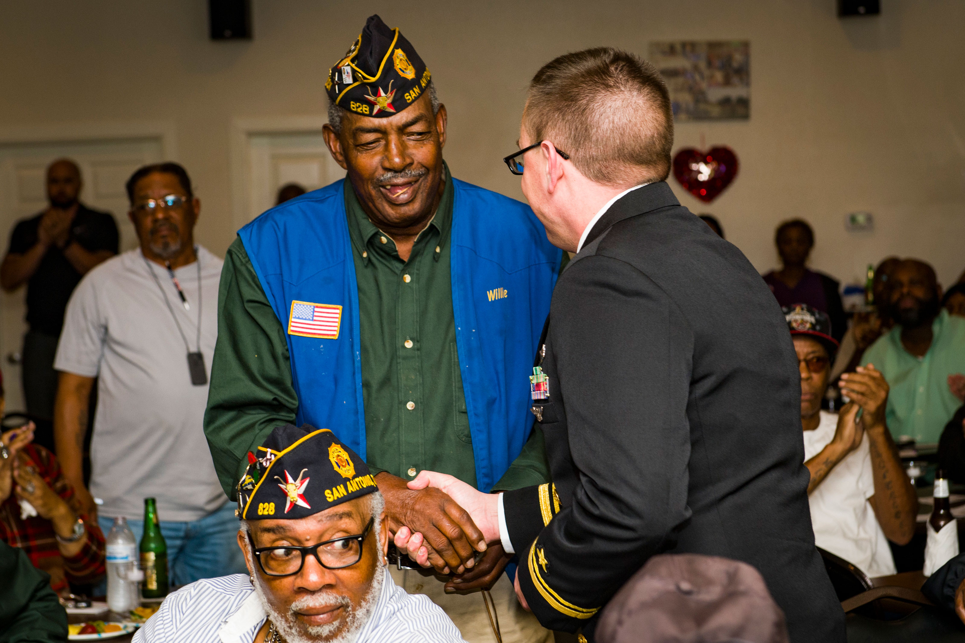Lt. j.g. Mack Jamieson gives a pin to an American Legion Fred Brock Post No. 828 Vietnam war veteran as part of San Antonio Navy Week. (U.S. Navy/Specialist 3rd Class Casey J. Hopkins)