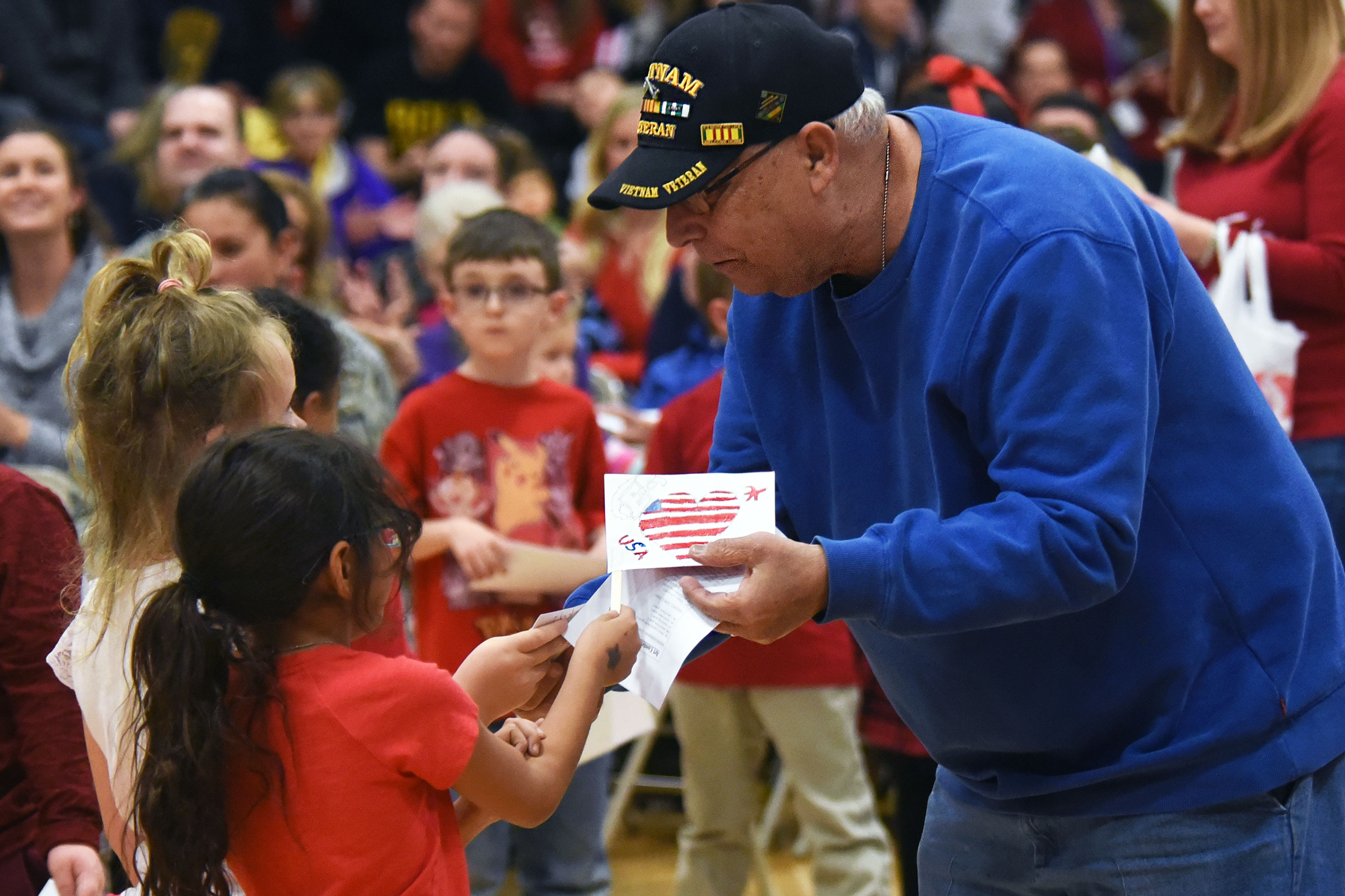 Ellicott students give thank you letters and hand-made flags to a Vietnam veteran during the Ellicott School District Veteran's Day ceremony at Ellicott, Colorado. The Ellicott community event honored veterans, both past and present. (U.S. Air Force/William Tracy)