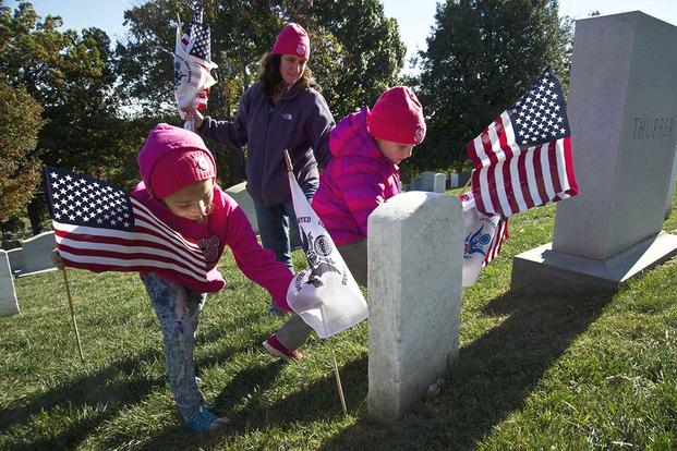 Coast Guard Lt. Cmdr. Melissa Ransom and her daughters participate in the annual Flags Across America event at Arlington National Cemetery in Arlington, Va., Nov. 5, 2016. (U.S. Coast Guard/PO2 Lisa Ferdinando)