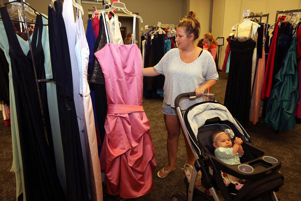 Michelle Walters selects a gown with her baby during Operation Ball Gown at Marine Corps Air Station Cherry Point, North Carolina. (U.S. Marine Corps/Jason Jimenez)