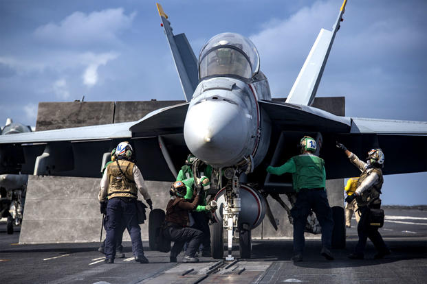 Sailors prepare an F/A-18F Super Hornet for takeoff on board the aircraft carrier USS Carl Vinson. (US Navy photo/Sean Castellano)