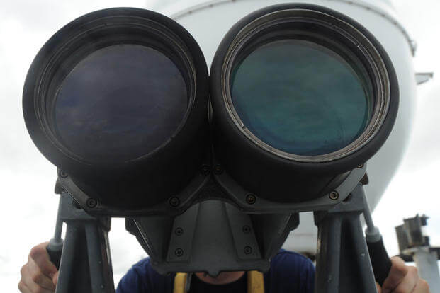 Coast Guard Seaman David Brink mans the binoculars as the Coast Guard Cutter Tampa prepares to anchor near the Panama Canal, Colón, Panama, July 27, 2017. (Coast Guard photo/Lisa Ferdinando)