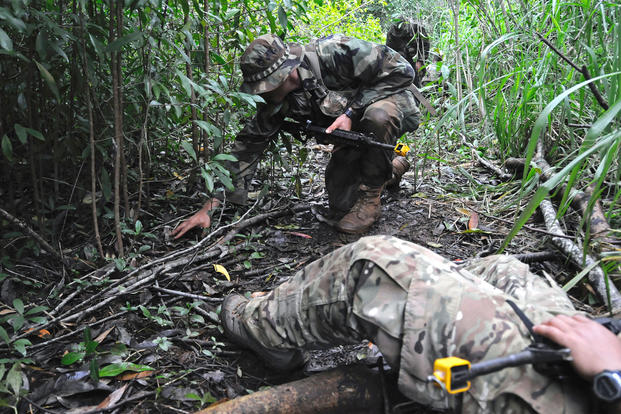A student at the Jungle Operations Training Center in Oahu, Hawaii, trains on checking for IEDs as he works his way back to an injured soldier. (US Army photo/Jay Koester)