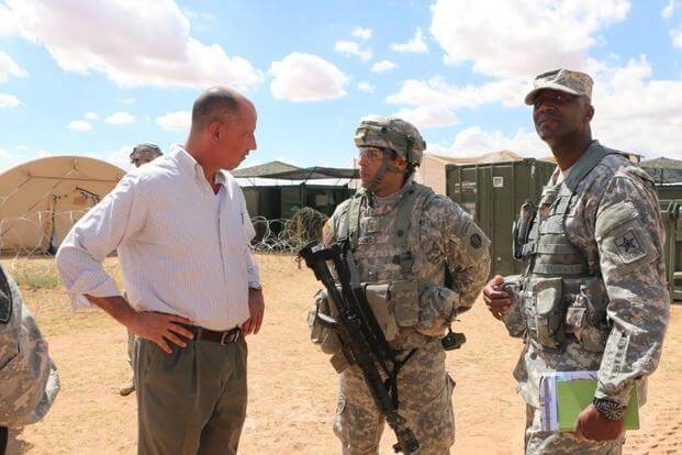 FILE - Kevin Fahey (left) and, Maj. Daniel Rodriguez and Col. Terrece Harris discuss new capabilities at the Expeditionary Base Camp at Fort Bliss, Texas. Fahey has been nominated for the post of assistant secretary of defense for acquisition. (ASA System of Systems Integration Directorate Public Affairs/ Vanessa Flores)