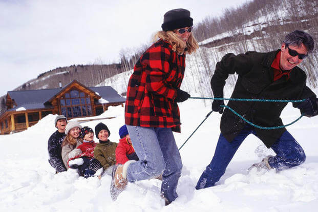 A couple pulling children on a sled