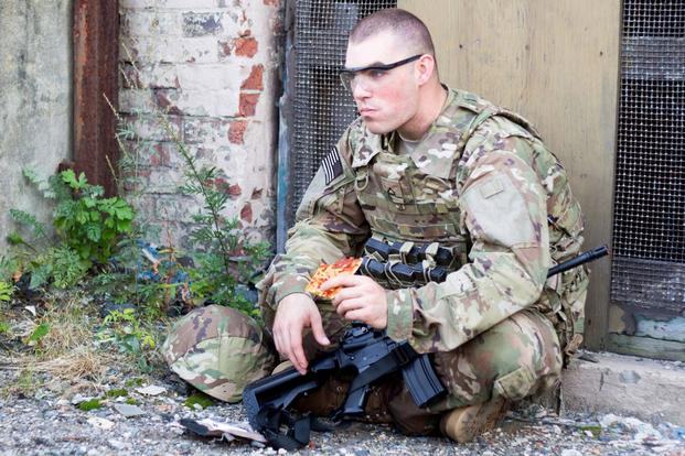 A soldier enjoys a Meal, Ready-to-Eat pizza developed by scientists in the Combat Feeding Directorate at the Natick Soldier Research, Development and Engineering Center. (U.S. Army Photo)