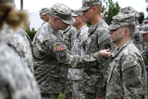 "Soldiers from the Utah and Wisconsin Army National Guard don the historic ""Old Abe"" patch during a June 2015 ceremony at Fort Campbell, Ky. (US Army photo/Terrance Rhodes)"
