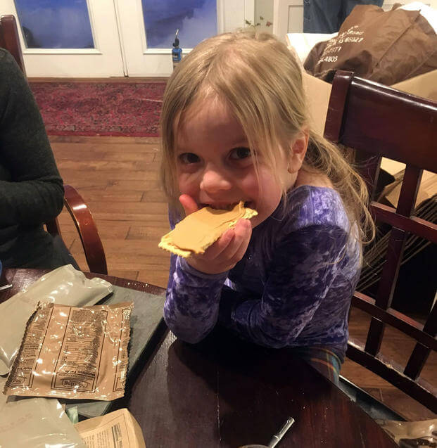 Angelina Vankirk, 6, smiles while taking a bite of a meal, ready-to-eat cracker with peanut butter during her Family's MRE night near Fort Drum, New York. (Courtesy of Patrick Vankirk)