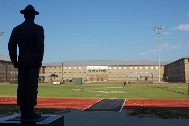 "The morning sun peaks over the rooftop of the Drill Sergeant Academy hitting the black letters from across the way, ""This We'll Defend."" The drill sergeant statue overlooks the physical fitness field at Fort Jackson, Aug. 12, 2015. (U.S. Army'Maj. Satomi Mack-Martin)"