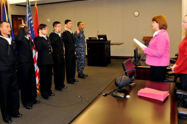 The first Navy sailors to participate in the MAVNI program are issued the oath of citizenship by Stacey Summers, branch chief from the U.S. Citizenship and Immigration Services Chicago field office. (US Navy photo/Scott Thornbloom)