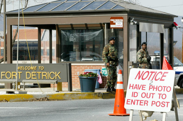 Two soldiers stand guard at the main gate of Fort Detrick in Frederick, Maryland.