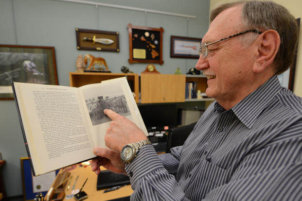 Johnie Webb, deputy of outreach and communications for the Defense POW/MIA Accounting Agency, points to a photo of him published in a book on U.S.-Vietnam diplomatic relations after the war inside his office at Joint Base Pearl Harbor-Hickam, Hawaii, March 13, 2018. Webb, a retired lieutenant colonel and Vietnam War veteran, was part of the first recovery team to enter Vietnam following the war in search of missing American service members. (U.S. Army photo/Sean Kimmons)