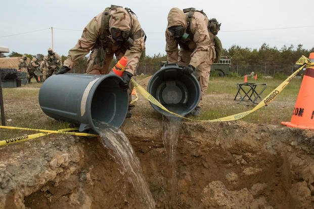 Soldiers with the Massachusetts Army National Guard, dispose of clean water used to clean notionally contaminated equipment on Joint Base Cape Code. The June, 2018 training was part of a Combined Arms Exercise which tests the mission readiness of combat support. (Massachusetts Army National Guard/Cody Kilduff)