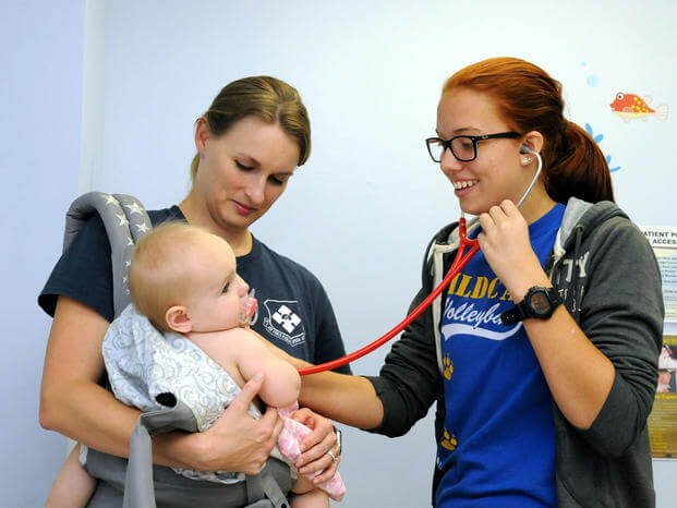 A student assists during a well baby check-up. (U.S. Navy/David D. Underwood, Jr.)