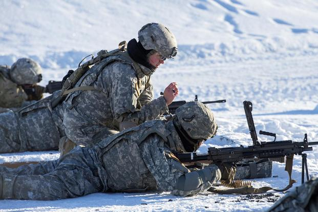 Sgt. Melissa Burdge, top center, assigned to the 17th Combat Sustainment Support Battalion, U.S. Army Alaska, coaches a fellow Soldier during M249 light machine gun live-fire training at Joint Base Elmendorf-Richardson, Alaska, Feb. 23, 2018. (U.S. Air Force/Alejandro Peña)