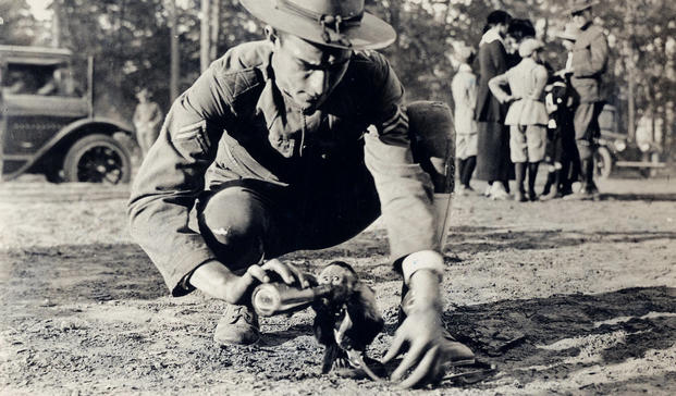 A World War I soldier plays with the unit mascot at Camp Wadsworth near Spartansburg, South Carolina. (Photo: National Archives and Records Administration)