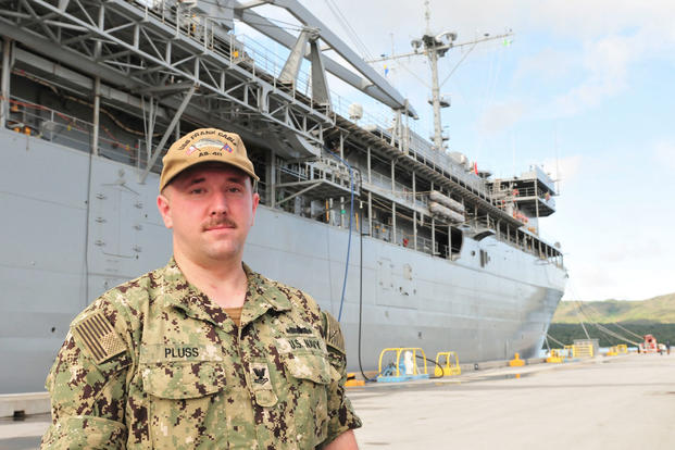 Navy Petty Officer 2nd Class Andrew Pluss, an electrician's mate assigned to the Guam-based submarine tender USS Frank Cable, stands in front of the ship at Naval Base Guam, July 18, 2018. Pluss helped the victim of an auto-pedestrian crash in Guam July 16. (U.S. Navy photo/Alana Chargualaf)
