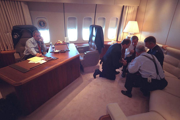 President George W. Bush talks on the telephone Sept. 11, 2001, as senior staff huddle aboard Air Force One. (Photo by Eric Draper, Courtesy of the George W. Bush Presidential Library)