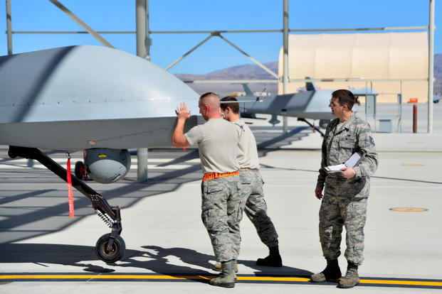 Tech. Sgt. Remington, a 432nd Maintenance Group quality assurance inspector, watches as a 432nd Aircraft Maintenance Squadron Tiger Aircraft Maintenance Unit team checks the weight and balance of an MQ-1 Predator on May 3, 2016, at Creech Air Force Base, Nev. (U.S. Air Force photo/Christian Clausen)