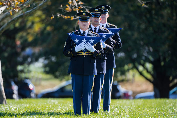 Soldiers hold folded American flags that will be present to family members. (Elizabeth Fraser/Arlington National Cemetery)