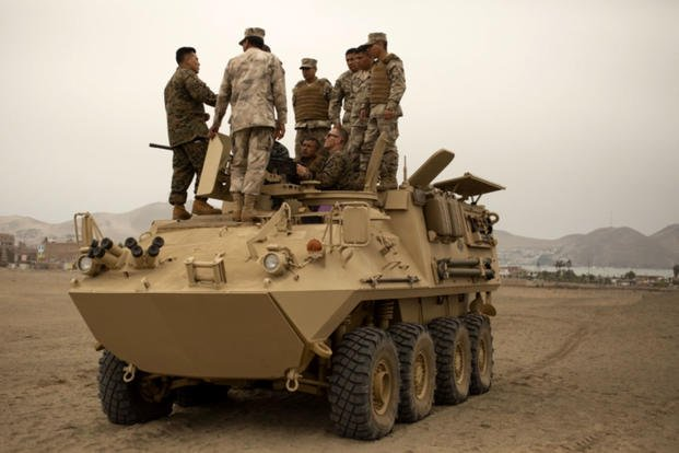 U.S. Marines and Peruvian naval infantrymen stand atop a Peruvian amphibious assault vehicle on Oct. 24, 2018, discussing mounted weapons handling. (US Marine Corps photo/ Frans E. Labranche)