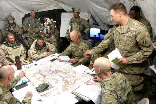 Capt. Timothy Cody, standing, briefs Col. Patrick O'Neal, commander of 2nd Armored Brigade Combat Team, and other leaders during a May 6 operations order at the National Training Center, Fort Irwin, California. (Matthew Cox/Military.com)