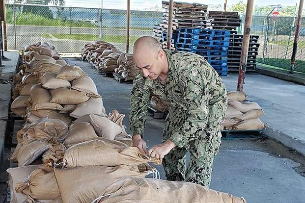 SW2 Matthew Koenig of Construction Battalion Maintenance Unit 202 fills sandbags to be placed around Naval Air Station Jacksonville, Florida, in preparation for Hurricane Dorian. Photo by Julie M. Lucas