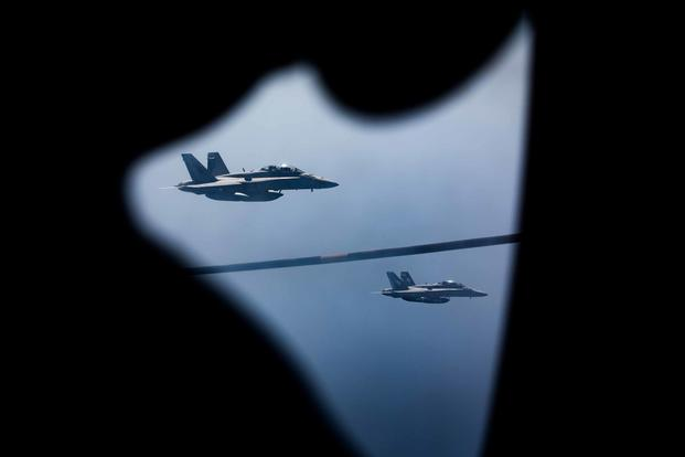 Two F/A-18D Hornets approach a KC-130J with Marine Aerial Refueler Transport Squadron 352 during a Special Purpose Marine Air-Ground Task Force-Crisis Response-Central Command aerial refueling exercise on Oct. 13, 2016. (U.S. Marine Corps photo by Cpl. Trever Statz)
