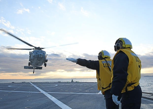 Sailors direct the launch of an MH-60S Sea Hawk helicopter from the USS Blue Ridge