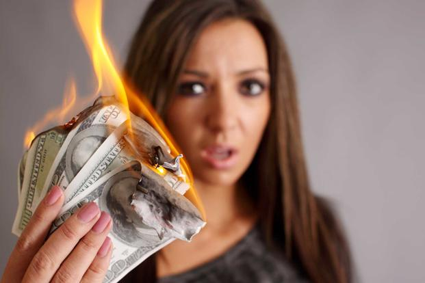 Woman holding a handful of burning cash