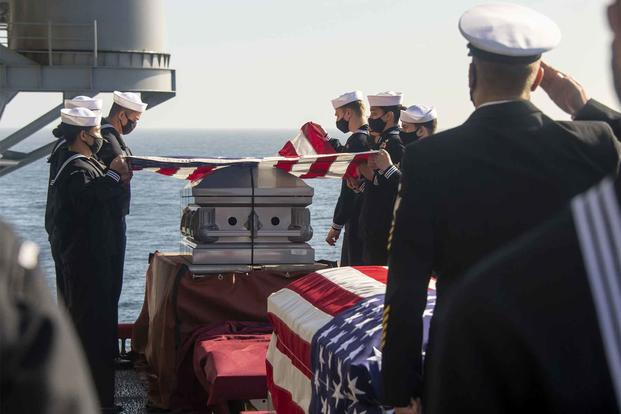 The crew of Wasp-Class amphibious assault ship USS Essex (LHD 2) holds a burial at sea for 25 service members and two spouses while at sea in the Pacific Ocean, March 29, 2021. (U.S. Navy)