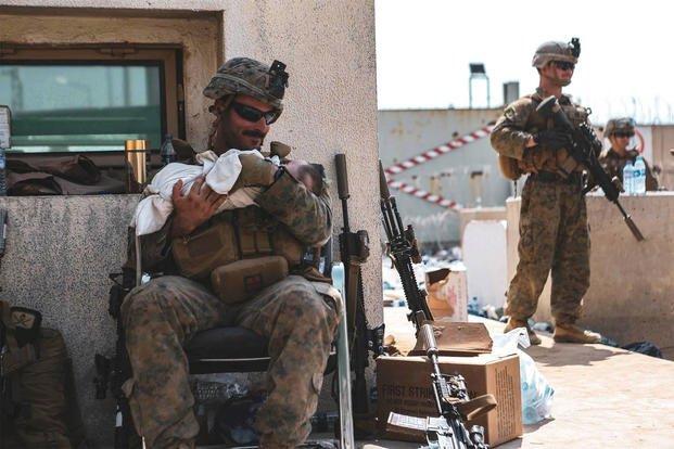 U.S. military service members comfort infants at Hamid Karzai International Airport in Kabul, Afghanistan.