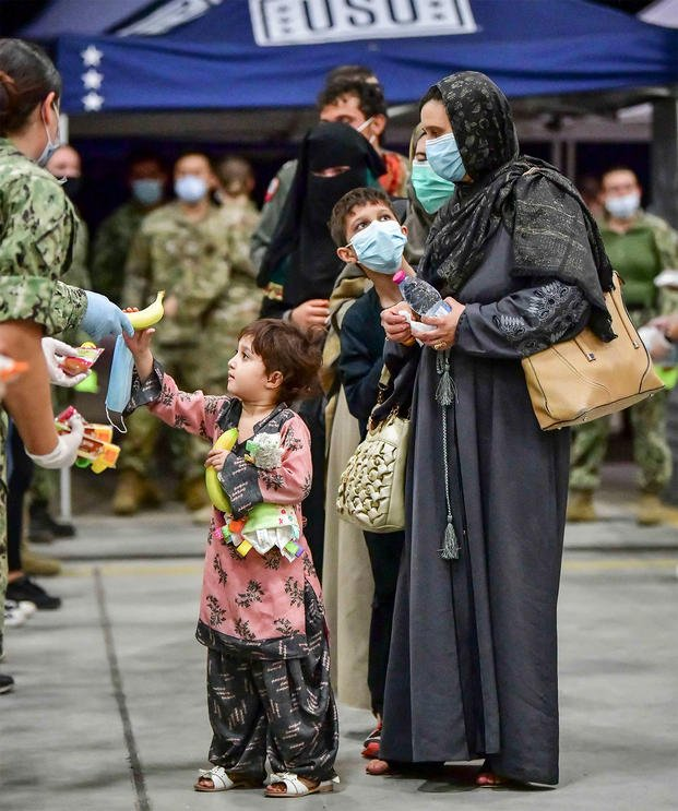 A family of Afghan evacuees receive food and masks.