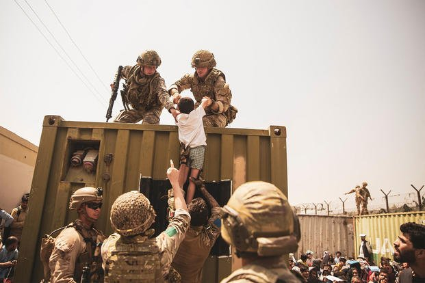 UK coalition forces, Turkish coalition forces, and U.S. Marines assist a child.