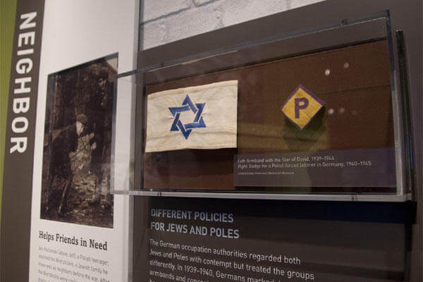 2013 photo shows an armband with the Star of David and a badge for a forced laborer in Germany at the United States Holocaust Memorial Museum.