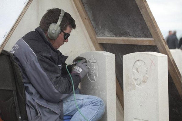An engraver works under a rain tent as he re-engraves the headstone of a WWI soldier at Tyne Cot cemetery in Zonnebeke, Belgium on Monday, April 15, 2013.