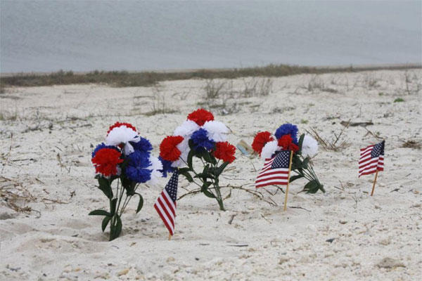 A small memorial stands in the sand along Highway 98 in Navarre, Fla., Thursday, March 12, 2015. (AP Photo/Northwest Florida Daily News, Jennie McKeon)