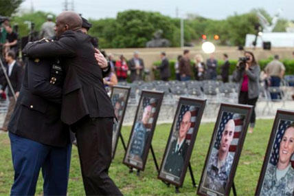 Pfc. James Armstrong, left, and Chief Warrant Officer 2 Christopher Royal hug as they look at pictures of co-workers killed in the 2009 Fort Hood shooting, Friday, April 10, 2015, at Fort Hood, Texas. (AP Photo/Austin American-Statesman, Rodolfo Gonzalez)