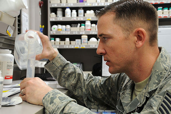 An Air Force pharmacy technician measures distilled water for medicine. (U.S. Air Force photo/Staff Sgt. Julius Delos Reyes)