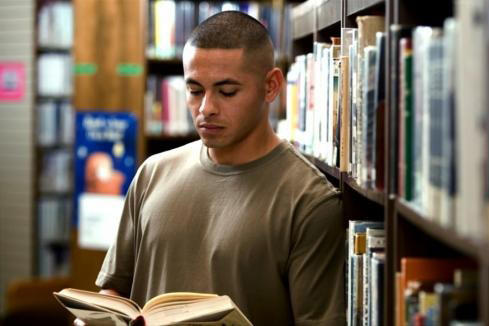 Marine reading a book in a library next too a bookshelf.