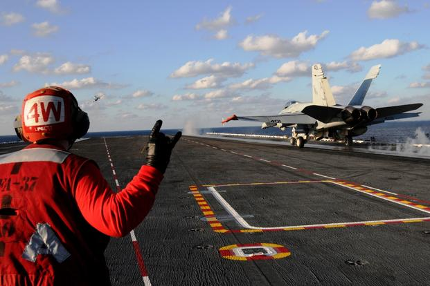 A sailor signals as an F/A-18C Hornet takes off on the flight deck aboard the aircraft carrier USS George H.W. Bush on Dec. 2, 2016, in the Atlantic Ocean. (U.S. Navy photo/Brooke Macchietto)