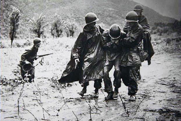 Two Army captains carry an exhausted Soldier off the battlefield in Korea. (U.S. Army photo)