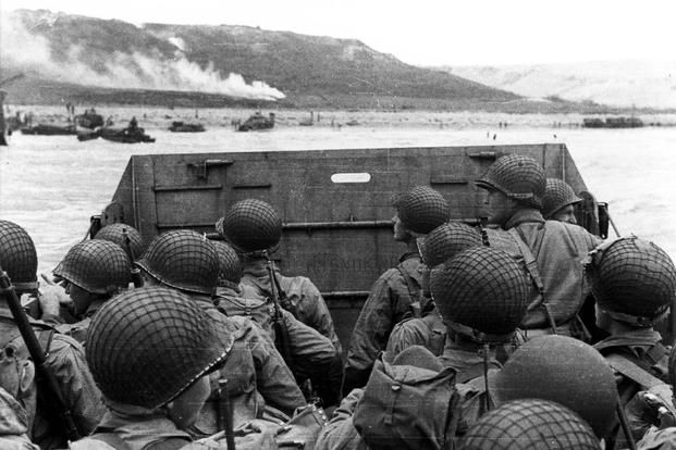American assault troops in a landing craft huddle behind the protective front of the craft as it nears a beachhead, on the Northern Coast of France. Smoke in the background is Naval gunfire supporting the land. 6 June 1944. (Photo: U.S. Army)