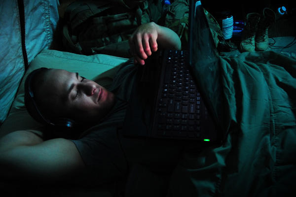 Soldier in bed with a laptop and headphones.