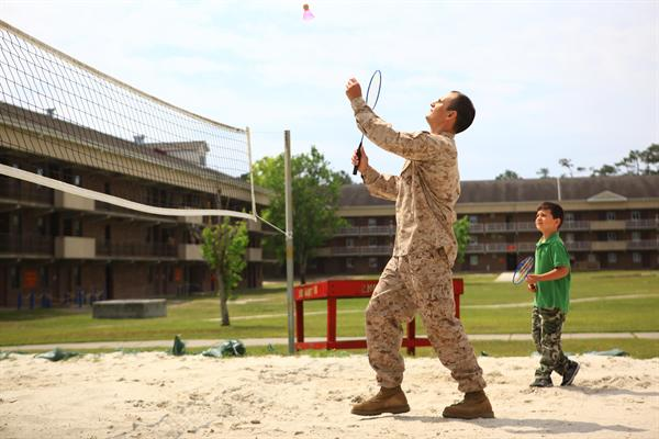 Servicemember and child playing badminton.