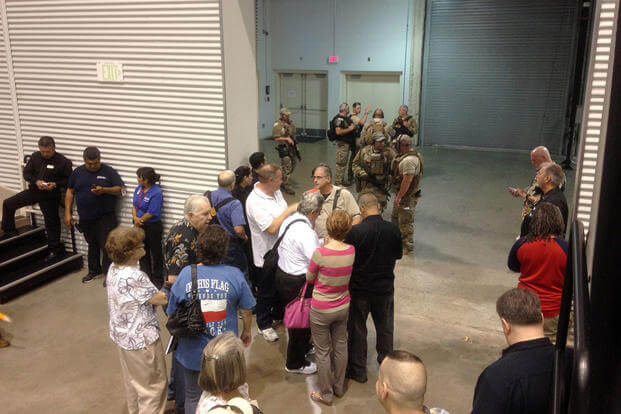 People are sequestered by members of the Garland Police Department inside the Curtis Culwell Center, Sunday, May 3, 2015, in Garland, Texas, after a shooting outside the building. Nomaan Merchant/AP