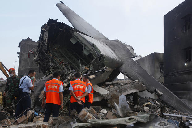 Investigators inspect the wreckage of the crashed air force transport plane in Medan, North Sumatra, Indonesia, on July 1, 2015. The Hercules C-130 crashed into a residential neighborhood in the country's third-largest city on June 30. Binsar Bakkara/AP