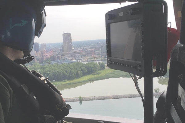 Petty Officer 2nd Class Adam Shaw, aboard a Coast Guard MH-65C Dolphin helicopter from Air Station Detroit, searches Lake Erie for Giusseppe Reinhart July 28, 2016. (U.S. Coast Guard/PO2 William Lawson)