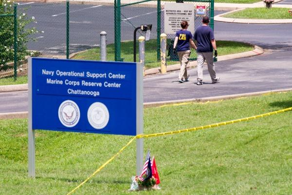 Investigators walk by the entrance of a Navy and Marine center in Chattanooga, Tenn., on Wednesday, July 22, 2015.(AP Photo/Erik Schelzig)